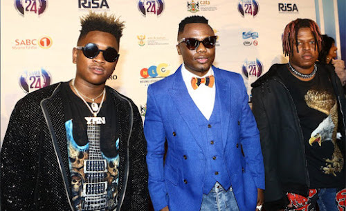 Dj Tira is flanked by members of the Destruction Boyz on the red carpert before the start of the SAMA 24 music awards.